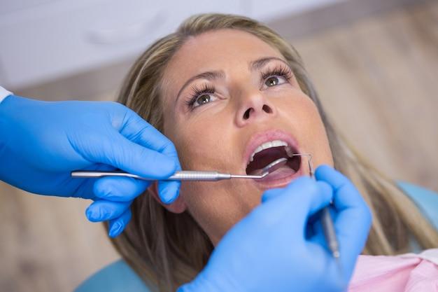 Tandarts die een vrouwelijke patiënt met hulpmiddelen onderzoekt