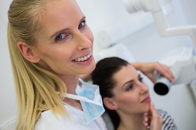 Tandarts die een vrouwelijke röntgenstraal van de patiëntentand nemen