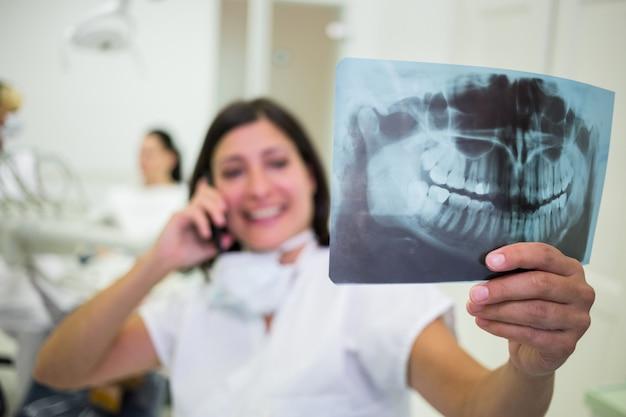 Tandarts die een x-ray rapport controleert terwijl het spreken op mobiele telefoon