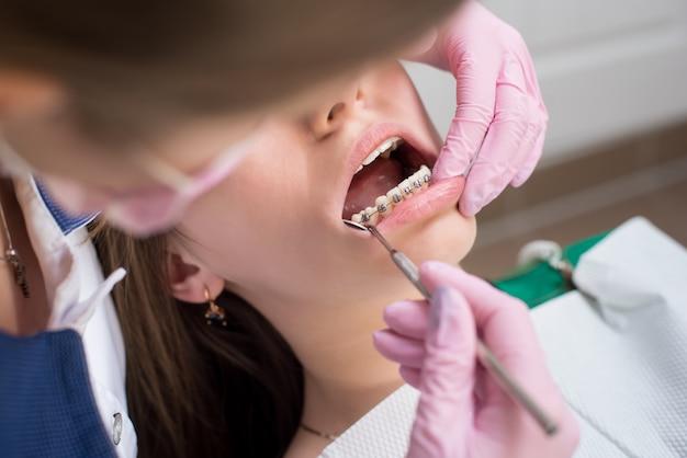 Tandarts die geduldige tanden met metaalsteunen controleren op tandkliniekkantoor