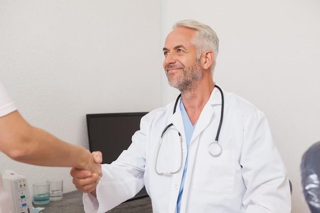 Tandarts die handen met zijn patiënt schudt