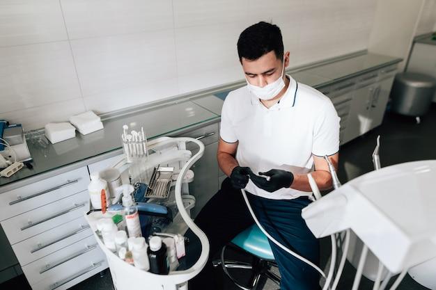 Tandarts die in bureau chirurgische instrumenten voorbereidt