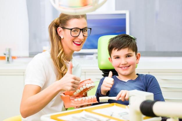 Tandarts die jongens schoonmakende tand verklaart