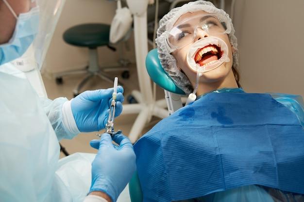 Tandarts die lokale anesthesie maakt die vóór de operatie wordt neergeschoten. patiënt die een tandartspraktijk bezoekt