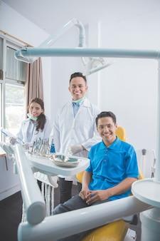 Tandarts die met mannelijke patiënt in tandkliniek glimlacht