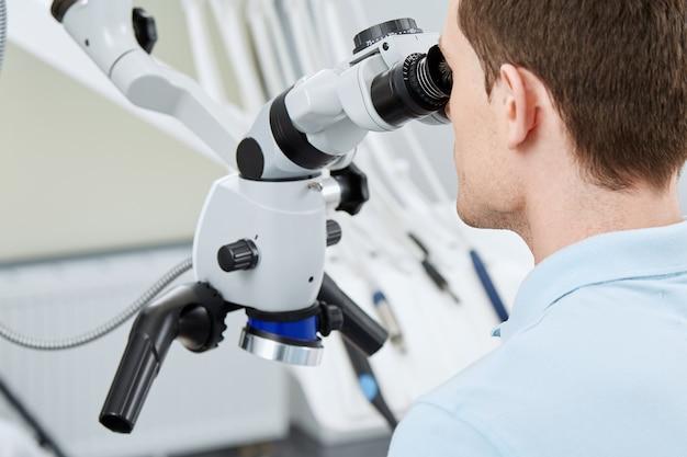 Tandarts die met moderne microscoop werkt