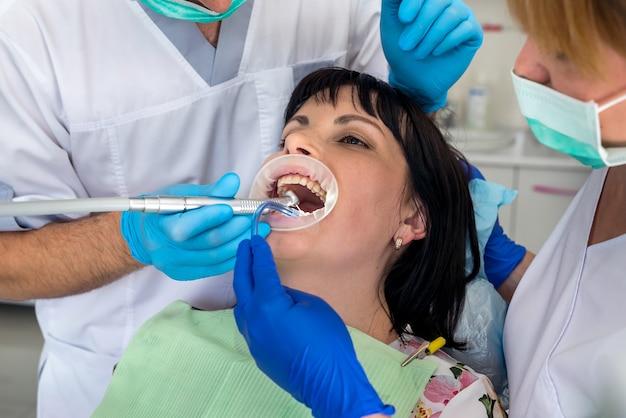 Tandarts die met patiënt in stoel, tandheelkunde werkt