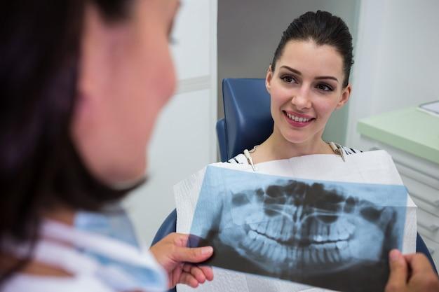 Tandarts die met patiënt over x-ray rapport bespreken