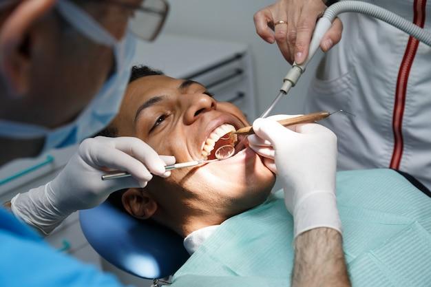 Tandarts die mondholte van de jonge mens onderzoeken die binnen in tandkliniek met medewerker werken.