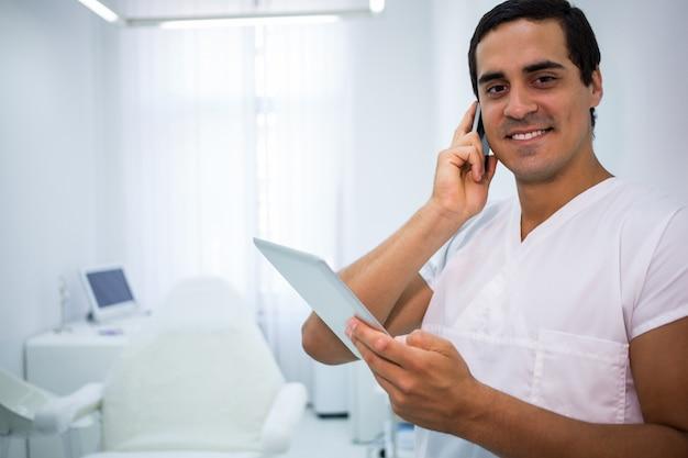 Tandarts die op mobiele telefoon spreekt en digitale tablet houdt