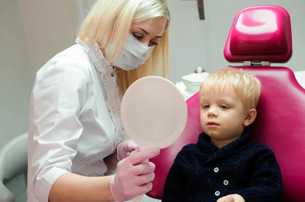 Tandarts die regelmatige tandcontrole aan kleine jongen doet.