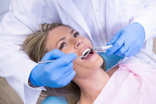 Tandarts die schuine spiegel houdt tijdens de behandeling van vrouw bij medische kliniek