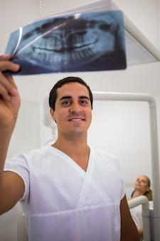 Tandarts die tand x-ray plaat bekijkt