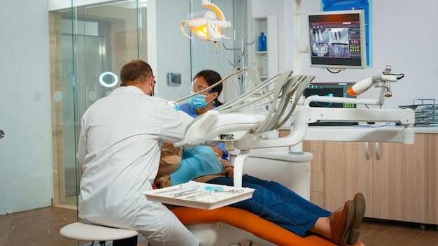 Tandarts die tanden behandelt aan hogere vrouwenpatiënt in kliniek die op stoel met open mond ligt. arts en verpleegster werken samen in een modern stomatologisch kantoor met een beschermingsmasker