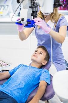 Tandarts die tanden van een jongen onderzoekt door microscoop