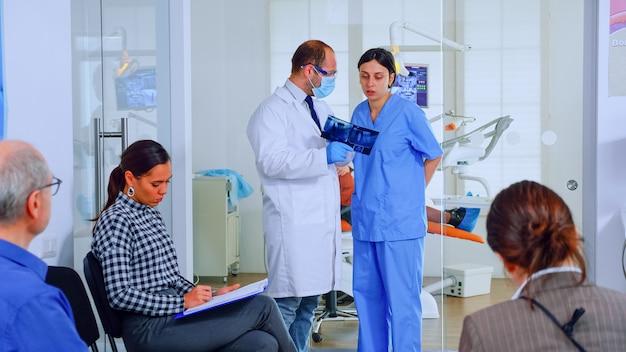 Tandarts die tandenröntgenstraal toont die het met nusre herzien. dokter en assistent werken in moderne drukke stomatologische kliniek, patiënten zitten op stoelen bij de receptie en vullen tandheelkundige formulieren in en wachten