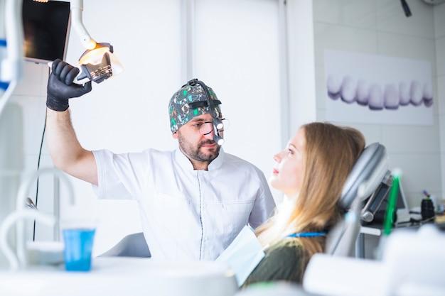 Tandarts die tandloupe verrekijkers draagt die vrouwelijke patiënt behandelen