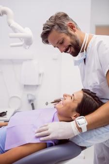 Tandarts die terwijl het onderzoeken van patiënt glimlacht