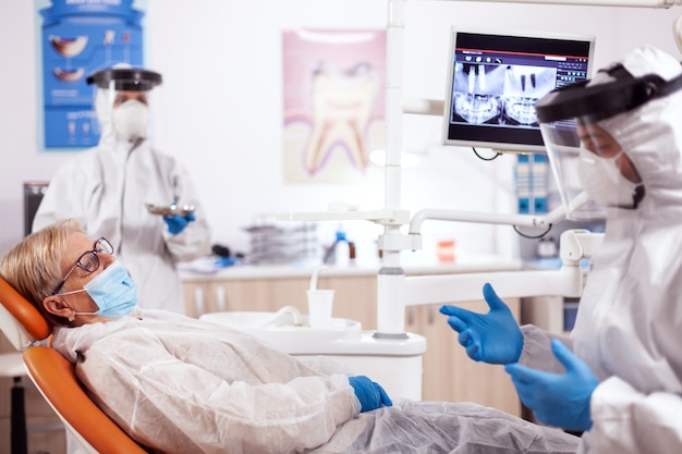 Tandarts die veiligheidsuitrusting draagt tegen coronavirus die over tandenbehandeling spreekt. oudere vrouw in beschermend uniform tijdens medisch onderzoek in tandheelkundige kliniek.