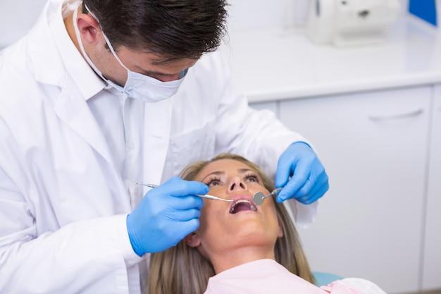 Tandarts die vrouw bij tandkliniek onderzoekt