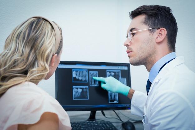 Tandarts die vrouw haar mondröntgenstraal op computer toont