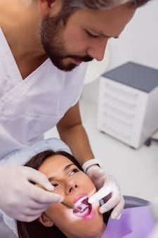 Tandarts die vrouwelijke geduldige tanden met een mondspiegel onderzoeken