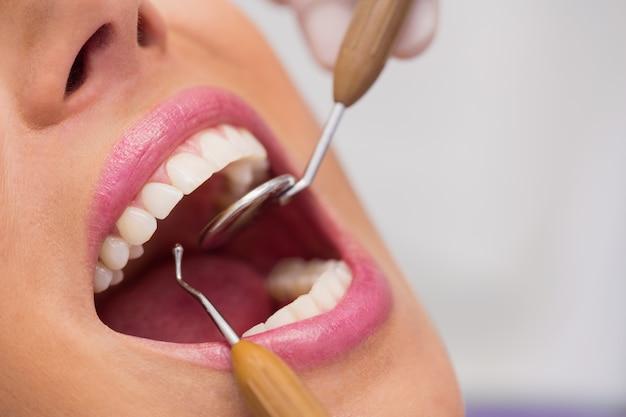 Tandarts die vrouwelijke geduldige tanden onderzoekt