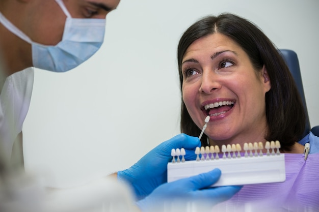 Tandarts die vrouwelijke patiënt met tandenschaduwen onderzoeken