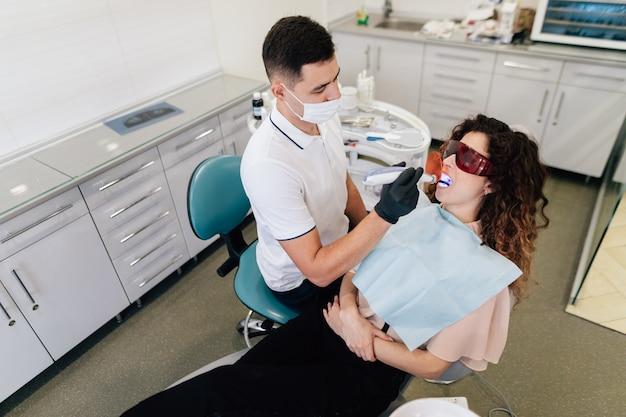 Tandarts die whitening op patiënt uitvoert