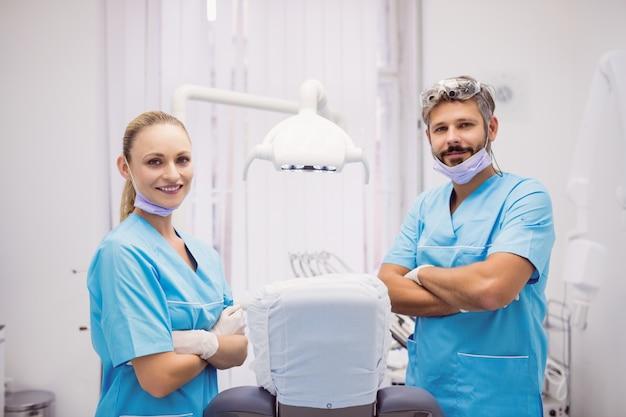 Tandarts die zich met wapens bevinden die bij tandkliniek worden gekruist