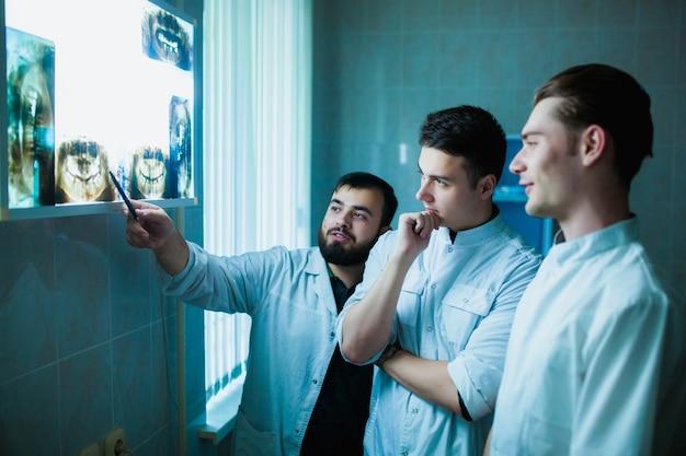 Tandarts. een groep professionele artsen bespreekt tandheelkundige behandeling op röntgenfoto's op kantoor. moderne medische opleiding.