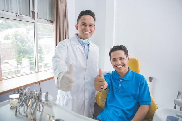 Tandarts en patiënt die duimen opgeven op tandartskantoor