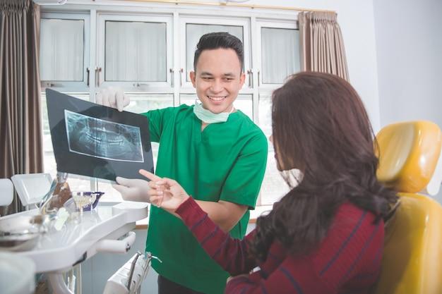 Tandarts en patiënt die röntgenstraal verklaren