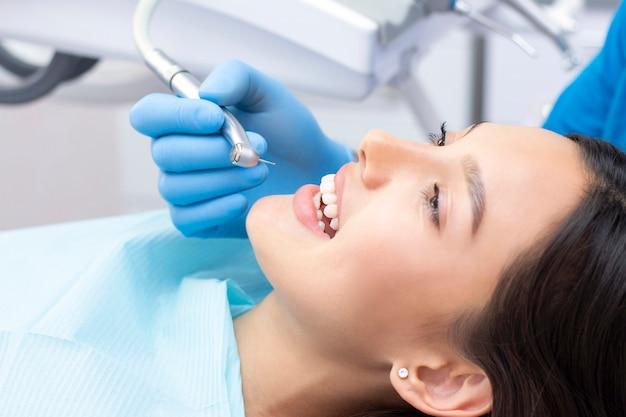 Tandarts en patiënt in de tandartspraktijk. vrouw die tanden heeft die door tandartsen worden onderzocht