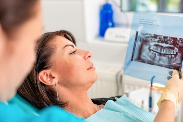 Tandarts en patiënt kijken naar röntgenfoto