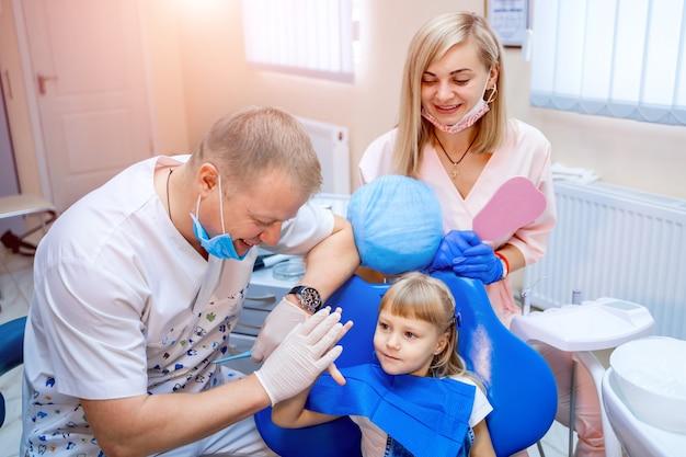 Tandarts en schattige jongen na het behandelen van tanden op het kantoor van de tandheelkundige kliniek, glimlachend en high-five geven