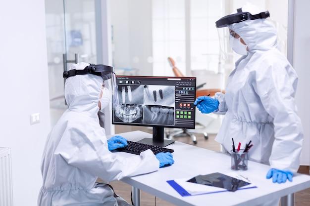 Tandarts en verpleegster bespreken problemen met de tanden van patiënten gekleed in ppe-pak. medisch specialist die beschermende kleding draagt tegen coronavirus tijdens wereldwijde uitbraak, kijkend naar radiografie in tandartspraktijk.
