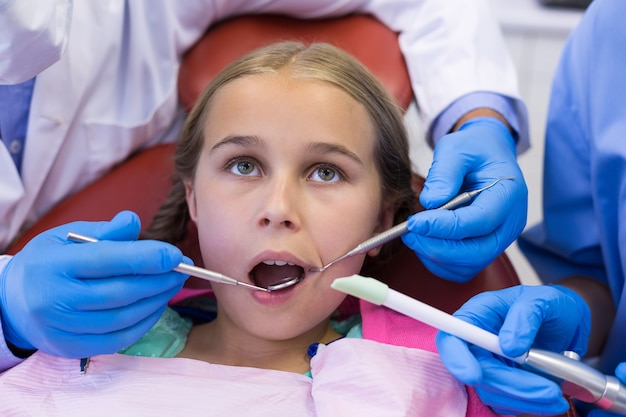 Tandarts en verpleegster die een jonge patiënt met hulpmiddelen onderzoeken