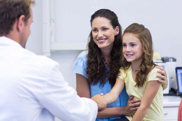 Tandarts hand met dochter schudden na tandheelkundig onderzoek
