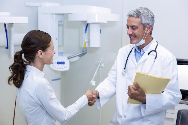 Tandarts hand schudden met vrouwelijke patiënt