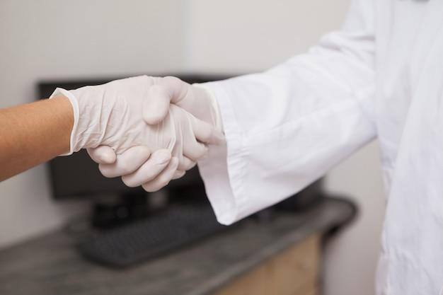 Tandarts handen schudden met zijn patiënt in de tandheelkundige kliniek