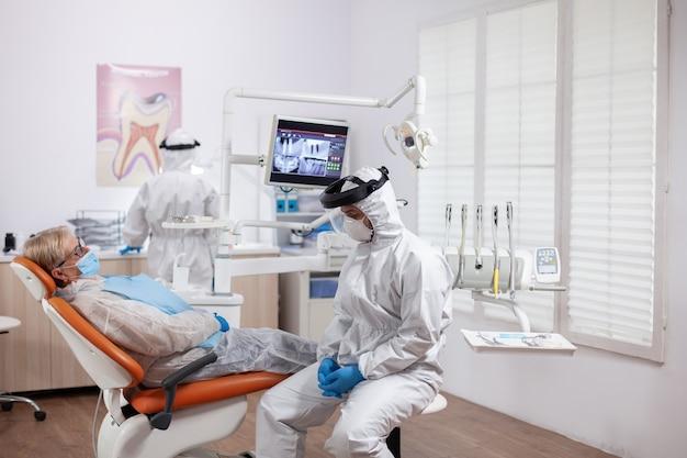Tandarts in beschermende kleding tegen coroanvirus met röntgenfoto van de patiënt op een stoel. oudere vrouw in beschermend uniform tijdens medisch onderzoek in tandheelkundige kliniek.