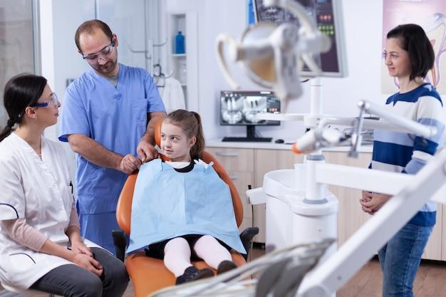 Tandarts in gesprek met ouder over mondhygine van kinderen voor gezondheid in tandartspraktijk. kind met haar moeder tijdens tandencontrole met stomatolog zittend op een stoel.