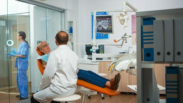 Tandarts in gesprek met senior patiënt in stomatologie stoel voor onderzoek. bejaarde die tandprobleem en tandpijn verklaart. behandeling tandheelkunde preventie