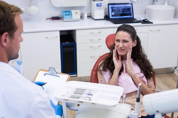 Tandarts in gesprek met vrouwelijke patiënt