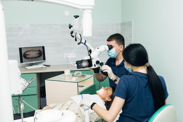 Tandarts in latexhandschoenen die geduldige tanden in kliniek onderzoeken. patiënt liggend met zijn open mond in het kantoor van de tandarts. stomatologist die onderzoek uitvoert met behulp van een microscoop