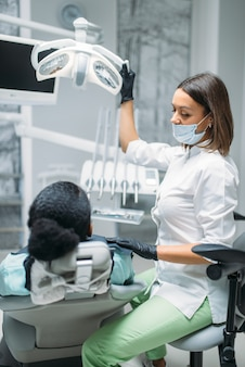 Tandarts in masker en handschoenen en vrouwelijke patiënt