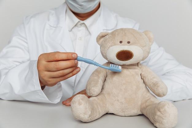 Tandarts in masker tanden van teddybeer schoonmaken