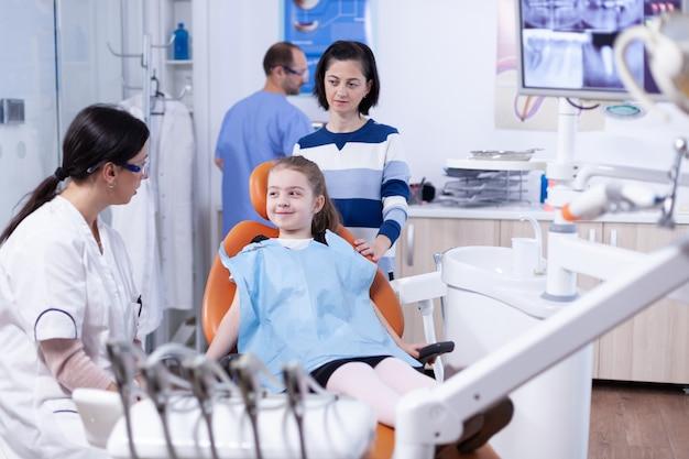 Tandarts in tandartspraktijk die klein meisje vertelt dat de behandeling niet pijnlijk zal zijn. kind met haar moeder tijdens tandencontrole met stomatolog zittend op een stoel.