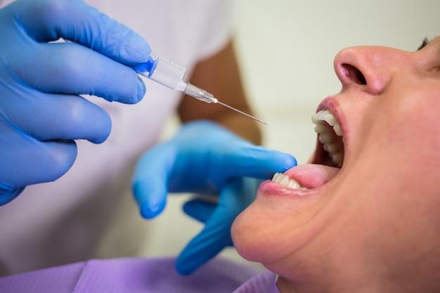 Tandarts injectie geven aan de vrouwelijke patiënt